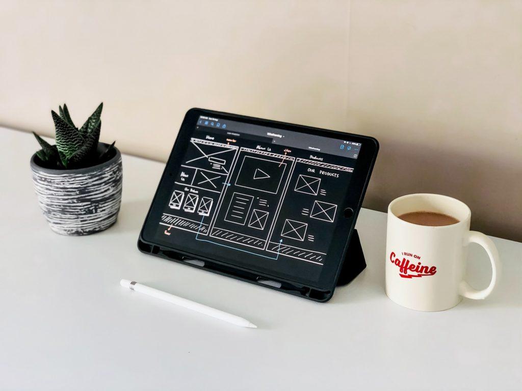 Egy drótvázat bemutató tablet áll az asztalon, mllette egy cserepes virág és egy bögre kávé