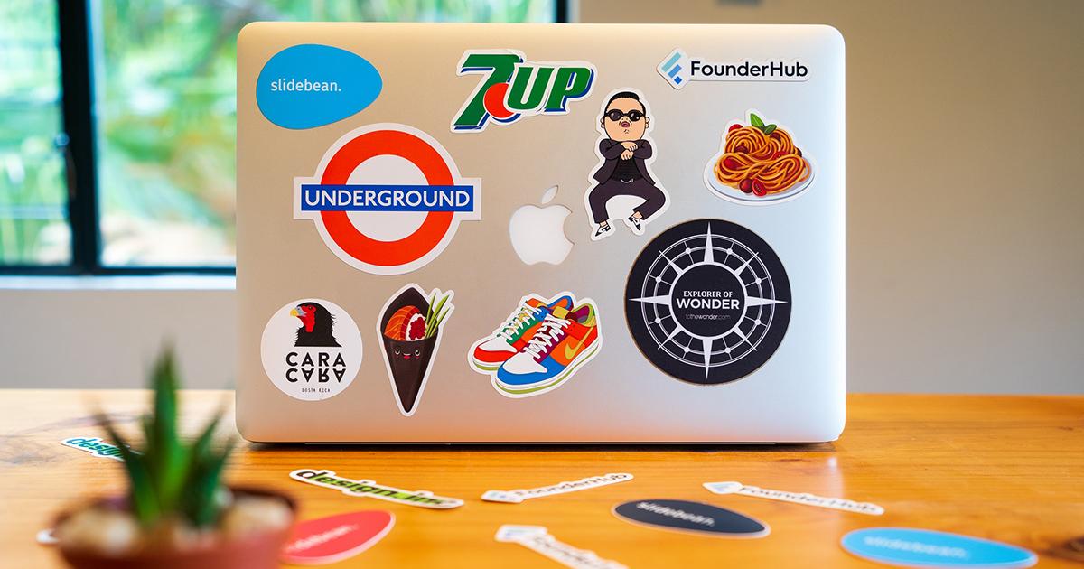 Laptop áll egy asztalon, a fedele teleragasztva logós matricákkal.