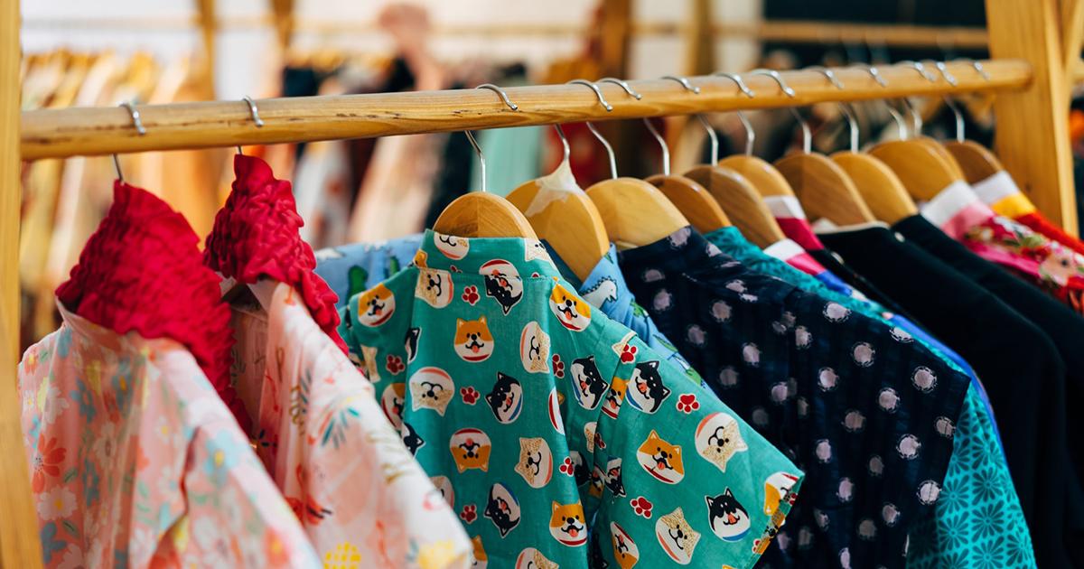 Színes, vidám ruhák lógnak egy boltban egy fa állványon