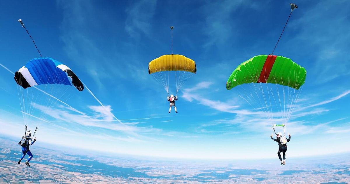 Három siklóernyős a levegőben