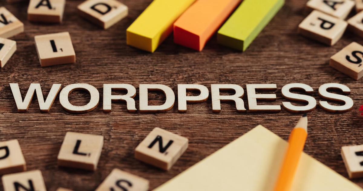 Fa betűkből kirakva egy asztalon, hogy Wordpress